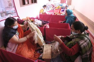 Photo: MyPad: Workers sorting through discarded clothing to create biodegradable cloth pads.