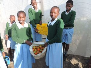 Photo: Kitechild: School children at the Fiwagoh home, showing the harvest from our greenhouse project, that works to fund their education.