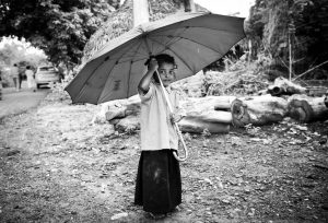 Title: Room for One More Photographer: Benjamin James Location: LAMP Mission, Nakkapali, Andra Pradesh, India. 2015 Description: A girl stands under an umbrella – twice her size – at the LAMP Mission Home. Through Kitechild, the home was able to reconstruct their roof to protect the sleeping area for the children from the common rains.